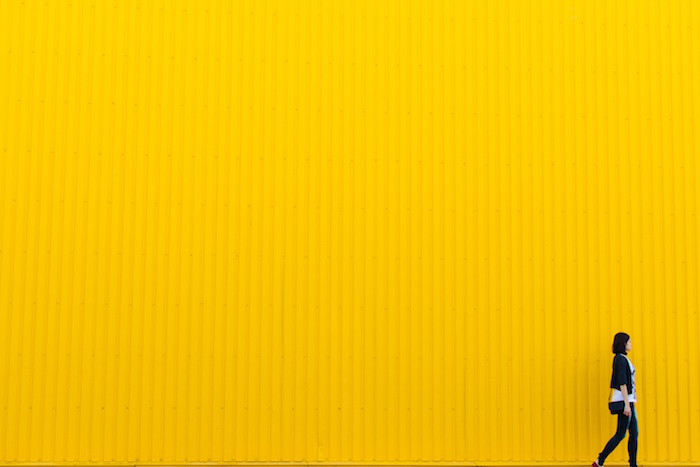 Woman walking in front of yellow wall