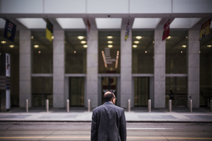 Man standing in front of corporate building