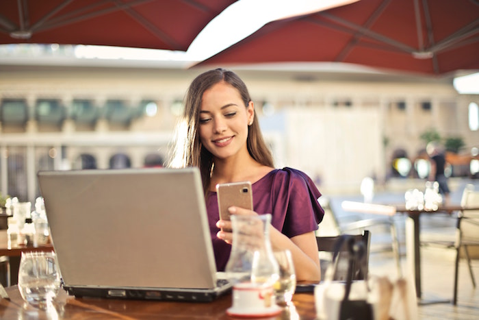 Woman smiles at open laptop while holding a mobile and checking LinkedIn